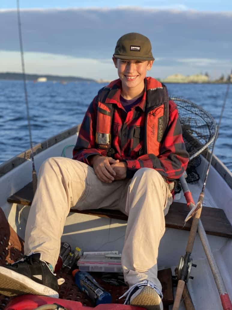 Young man in fishing boat smiling with fishing poles and net.